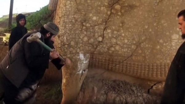 A still image taken off an ISIS video released in February 2015, allegedly showing a militant destroying the statue of Lamassu, an Assyrian diety, with a sledgehammer.