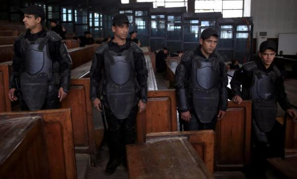 In this Feb. 28, 2015 file photo, Egyptian policemen stand guard in front of the courtroom defendant's cage during a verdict hearing on a case that stems from clashes near the Muslim Brotherhood's headquarters on June 30, 2013, in Cairo. Egypt executed an Islamist on Saturday, the first death sentence carried out against a supporter of the banned Muslim Brotherhood under President Abdel Fattah El-Sissi.