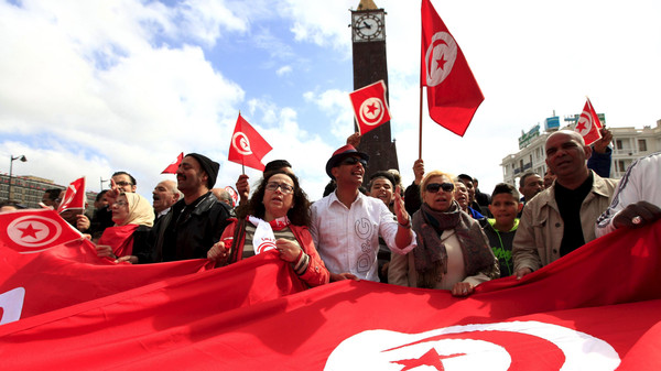 Tunisian protesters shout slogans as they wave banners and their national flag during a demonstration on Bourguiba Avenue, capital of Tunis, March 20, 2015, during Independence Day celebrations marking the 58th anniversary of independence in Tunis.
