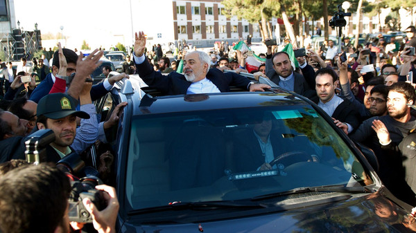 Iranian Foreign Minister Mohammad Javad Zarif (C) greets people as the nuclear negotiating committee arrive at Mehr Abad Airport in Tehran on April 3, 2015.