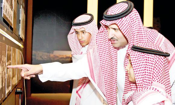 Madinah Gov. Prince Faisal bin Salman points to a photo at the King Fahd Exhibition in Riyadh.