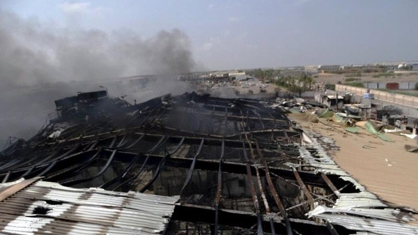 Smoke rises from a milk factory hit by an air strike in Yemen's western port city of Houdieda April 1, 2015.