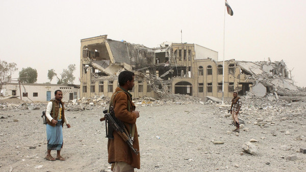Police troopers stand near the building of police headquarters, destroyed by Saudi-led air strikes, in Yemen's northwestern city of Saada.