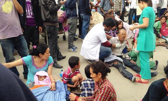 People injured in an earthquake receive treatment outside the Medicare Hospital in Katmandu, Nepal, on Saturday.