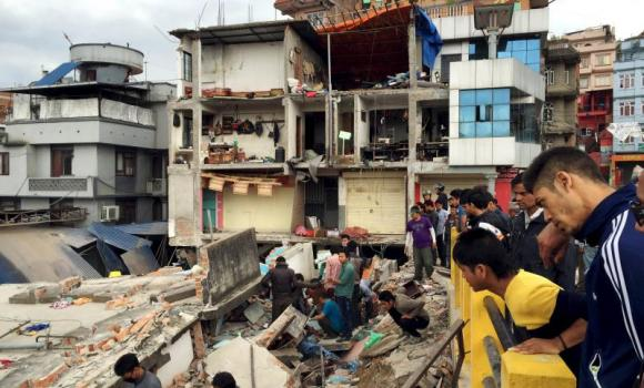 People survey a site damaged by an earthquake in Katmandu, Nepal, on Saturday.