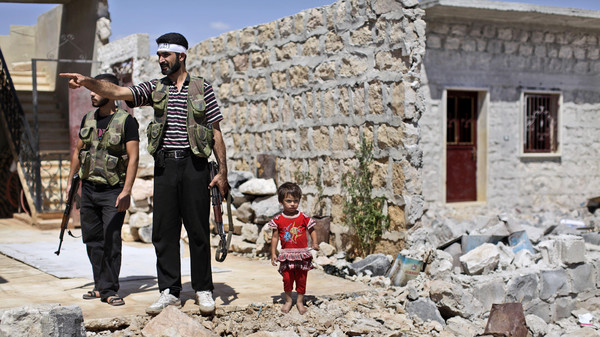 A Syrian child stands next to rebel fighters checking a house that was damaged in bombing by government forces in Marea, on the outskirts of Aleppo, Syria, Tuesday, Sept. 4, 2012.