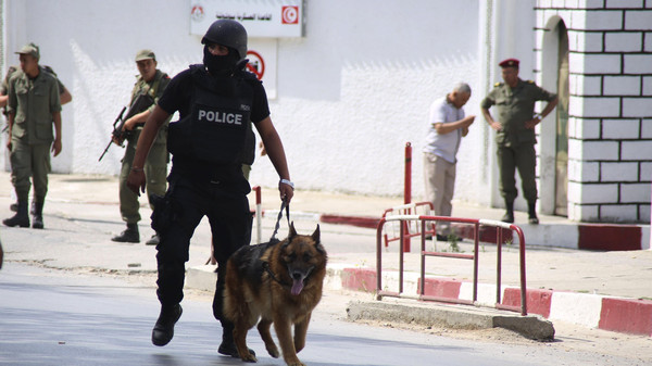 A Tunisian anti-terrorism brigade officer leads his dog after a shooting at the Bouchoucha military base in Tunis.