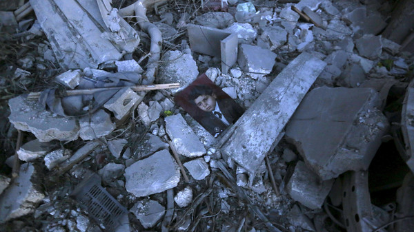 A picture lies amidst debris of collapsed buildings after what activists said was a barrel bomb dropped by forces loyal to Syria's President Bashar al-Assad in the Al-Qatrgi neighbourhood of Aleppo.