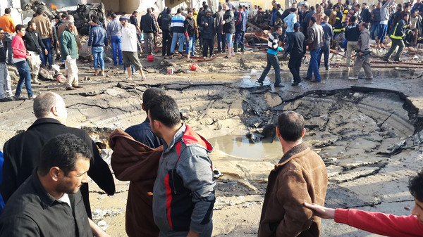 Egyptians gather around the crater following a bombing that struck a main police station in the capital of the northern Sinai province in el-Arish, Egypt, Sunday, April 11, 2015.