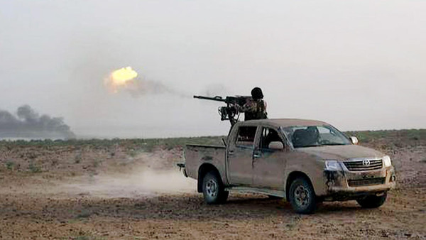 In this picture released on Wednesday, May 20, 2015 by the website of Islamic State militants, an Islamic State fighter fires his weapon during a battle against Syrian government forces on a road between Homs and Palmyra, Syria.