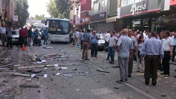 People stand at the site of an explosion at the office of pro-Kurdish People's Democratic Party (HDP) in Mersin on May 18, 2015.