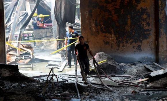 Fire investigators look for evidence amongst the ruins of a footwear factory in suburban Manila.