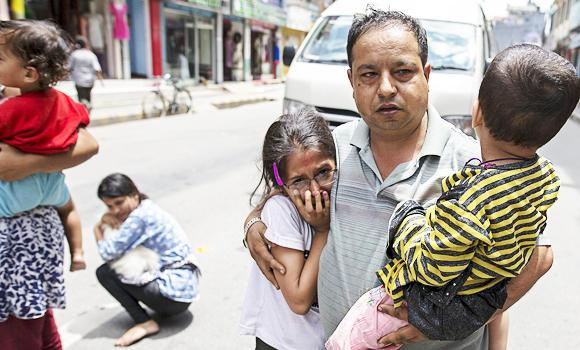 Local residents evacuate onto a street minutes after an earthquake in central Kathmandu, Nepal, May 12, 2015.