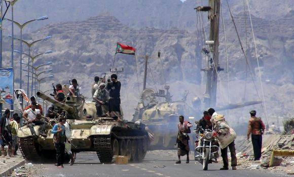 Southern Popular Resistance fighters gather on a road during fighting against Houthi fighters in Yemen's southern city of Aden on Sunday. May 3, 2015. The Saudi-led coalition battling rebels in Yemen denied reports that a major ground force had landed Sunday in Aden.