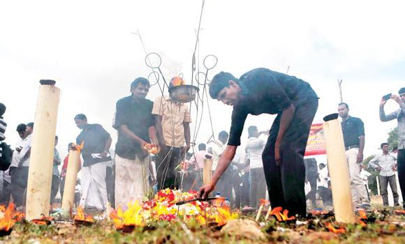 Sri Lanka's ethnic Tamil political activists offer flowers at a makeshift monument in Mullivaikkal where thousands of people were killed in fierce fighting between the army and Tamil Tiger rebels, on Monday.
