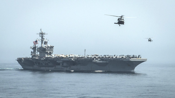 Helicopters fly from the aircraft carrier USS Theodore Roosevelt during a resupply mission with the aircraft carrier USS Carl Vinson in the Gulf of Oman.