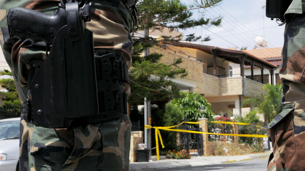Riot police stand guard outside of the house, left behind tree, which was discovered to contain some two tons of a chemical compound in southern costal city of Larnaca, Cyprus, on Saturday, May 30, 2015.
