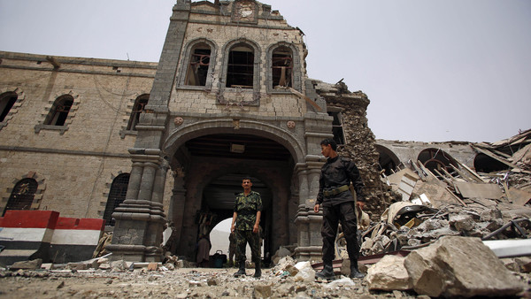 Shiite rebels known as Houthis wearing army uniforms stand guard in front of Yemen's Defense Ministry building after it was damaged by Saudi-led airstrikes in Sanaa, Yemen.