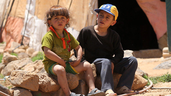 Syrian children sit outside a tent in a makeshift camp for refugee farm workers in northern Jordan.