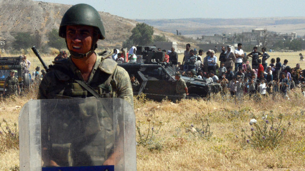 Turkish soldiers stand as people from the Syrian town of Ayn al-Arab or Kobani wait to cross into Turkey following the attacks by IS militants as seen from the Turkish side of the border in Suruc, Turkey, Thursday, June 25, 2015.