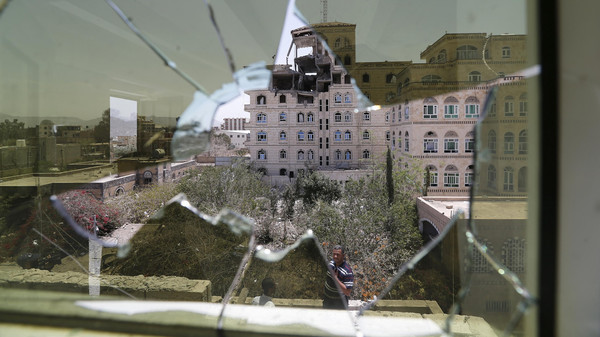 Damage in the building of the Houthi movement's politburo is seen through a broken window of an adjacent house.