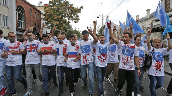 Uighurs living in Turkey and their supporters wear T-shirts with fake blood, representing Uighurs who have died in China's far-western Xinjiang Uighur region, during a protest in Istanbul, Saturday, July 4, 2015.