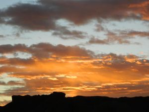 Clouds highlighted with the sun's orange rays of morning light cresting over the eastern buttes.