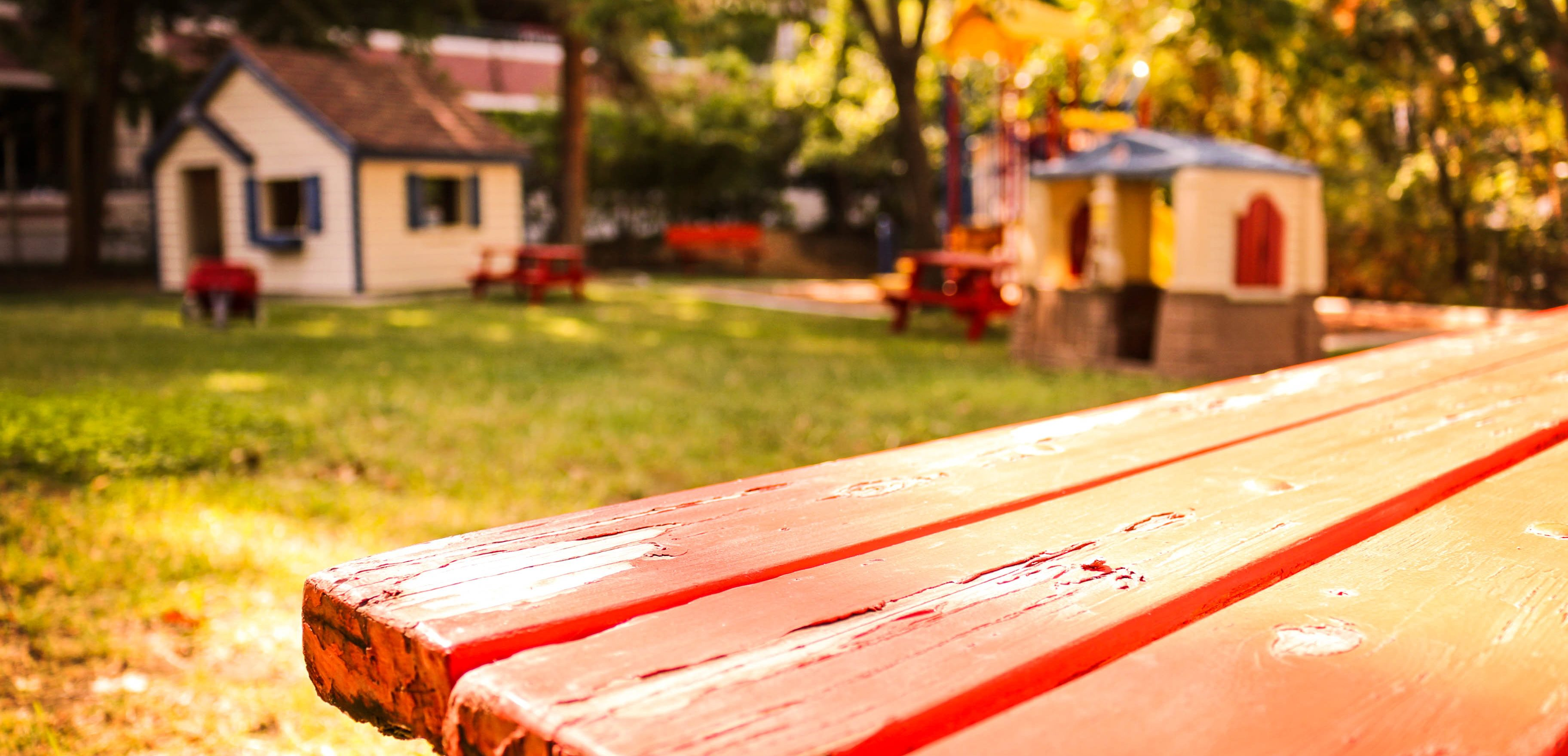 Picture of a backyard with a bench, two playhouses, and play structure