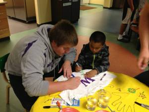 A boy colors on a shirt with a volunteer