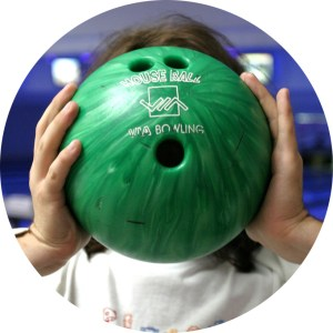 A lady holds a bowling ball in front of her face