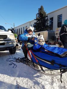 Jens and his dad on a dogsled at the start of the Iditarod