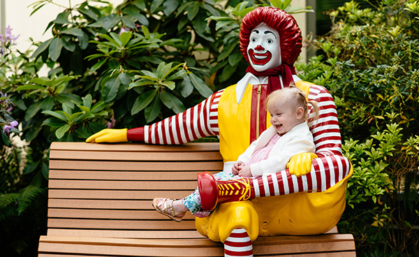 Constance sits in the lap of a Ronald McDonald statue at the Seattle House.
