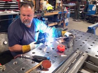 SMF shop employee welding on metal table