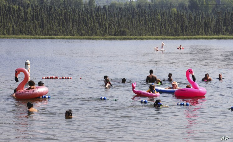 Children play with inflatable flamingos and other creatures at Goose Lake Friday, July 5, 2019, in Anchorage, Alaska. The official temperature on Thursday, July 4, reached 90 degrees for the first time in Anchorage and hot weather is expected to…