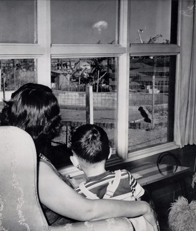A mom and her son watch the mushroom cloud after an atomic test 75 miles away, Las Vegas, 1953