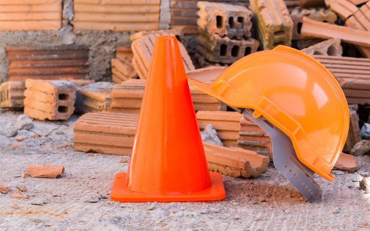 Helmet, cone and broken bricks at construction site.