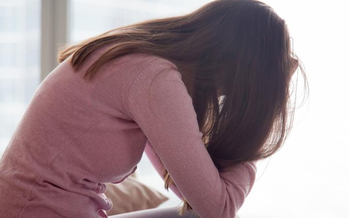 Young depressed woman sitting alone holding her head in hands, sad girl, problems at work, troubles in relationships,
