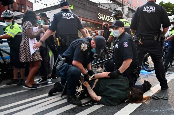 """Police officers cuff a protestor during a """"Black Lives Matter"""" protest near Barclays Center on May 29, 2020 in the Brooklyn borough of New York City, in outrage after George Floyd, an unarmed black man, died while being arrested"""
