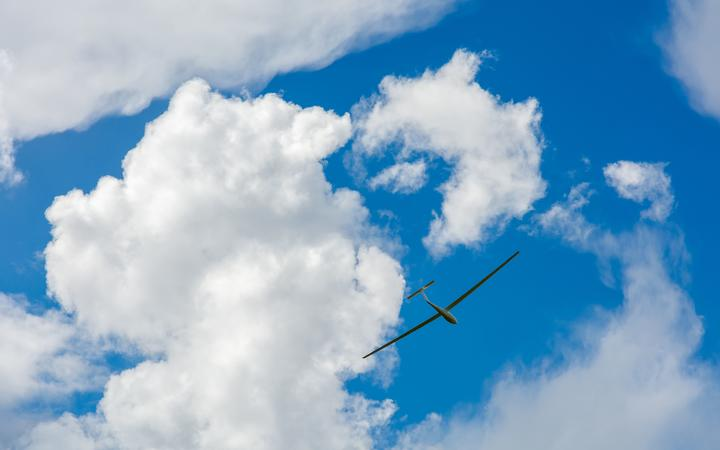 A Glider flying in bleu sky with big white clouds. The glider is a plane that has no engine