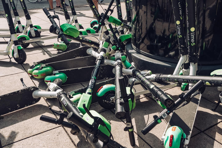 Lime e-scooters dumped on a pavement.