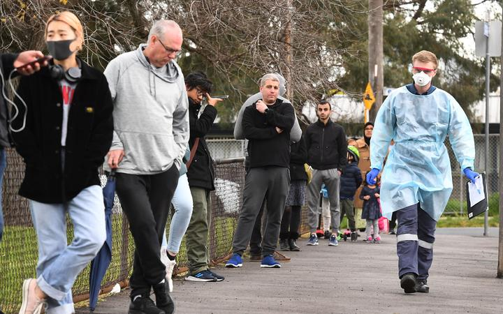 A health worker (R) takes details as people queue during COVID-19 coronavirus testing in a park in the Melbourne suburb of Brunswick West on July 2, 2020.