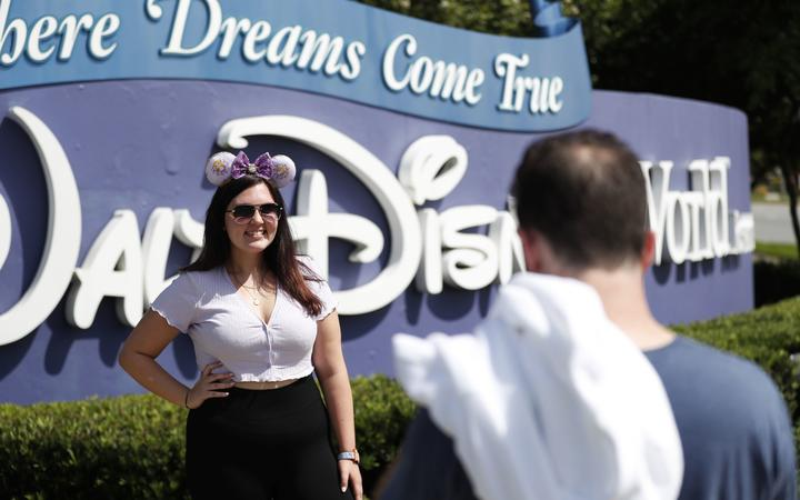 LAKE BUENA VISTA, FL - JULY 09: Michael Callahan (R) takes a photo of his friend Sarah Breland near the Walt Disney World theme park entrance World on July 9, 2020 in Lake Buena Vista, Florida.