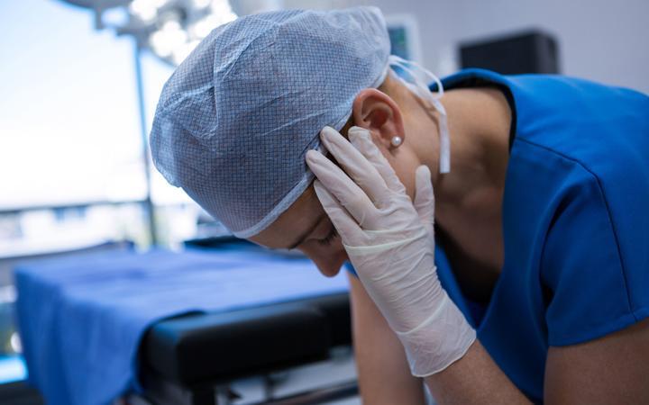Sad female nurse sitting in operation theater at hospital