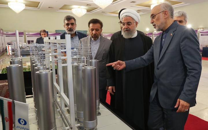 "Handout picture by the Iranian presidential office shows, Iranian President Hassan Rouhani (second left) with head of Iran's nuclear technology organisation Ali Akbar Salehi (right) during the ""nuclear technology day"" in Tehran in 2019."