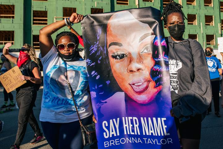 Two women hold a sign of Breonna Taylor during a rally on 18 September 2020 in Louisville, Kentucky.