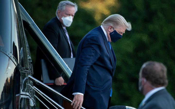 White House Chief of Staff Mark Meadows (L) watches as US President Donald Trump (C) walks off Marine One while arriving at Walter Reed Medical Center in Bethesda, Maryland on October 2, 2020.