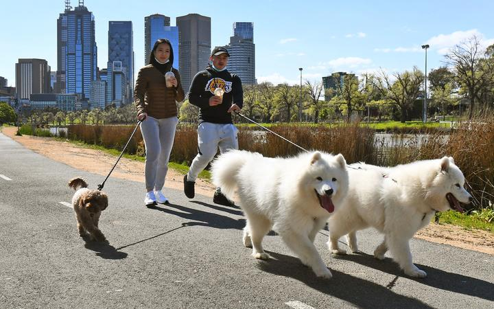 People walk their dogs along the banks of the Yarra River in Melbourne on September 27, 2020 as an overnight curfew in Australia's second-biggest city will be lifted from September 28,
