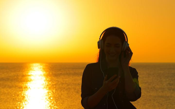 Front view of a woman silhouette listening to music at sunset on the beach