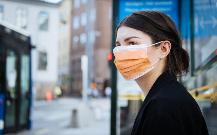 A young woman wearing a face mask at a bus stop.