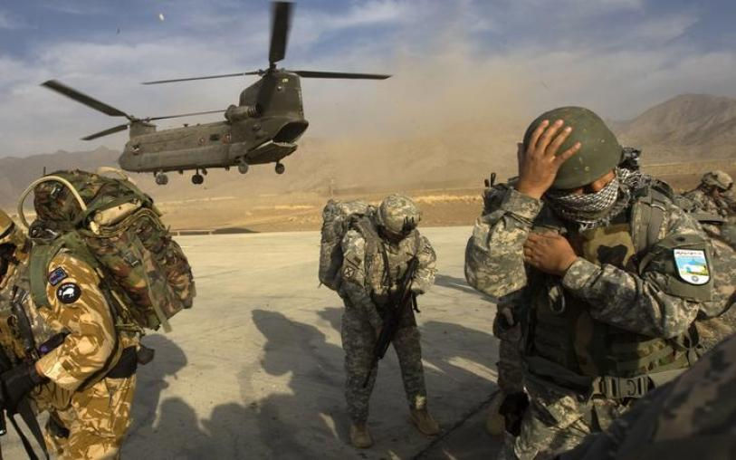 US Army soldiers from 2-506 Infantry 101st Airborne Division, Afghan National Army soldiers and a New Zealand Army soldier take cover as a CH-47 Chinook helicopter lands to transport them nto the Spira mountains in Khost province, in November 2008.  AFP PHOTO/DAVID FURST (Photo by DAVID FURST / AFP)